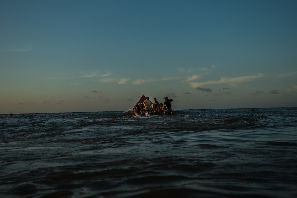 FALCÓN, VENEZUELA - SEPTEMBER 26, 2016: Undocumented migrants leaving on a smuggler's boat that will illegally take them from Venezuela to Curaçao. Undocumented migrants here have mortgaged property, sold kitchen appliances and even borrowed money from the same smuggling rings that pack them on the floorboards alongside drugs and other contraband. The journey to Curaçao takes them on a 60-mile crossing filled with backbreaking swells, gangs of armed boatmen and coast guard vessels looking to capture migrants and send them home. Then, after being tossed overboard and left to swim ashore, they hide in the brush to meet contacts who spirit them anew into the tourist economy of this Caribbean island. They clean the floors of restaurants, work in construction, sell trinkets on the street, or even solicit Dutch tourists for sex. But at least, the migrants say, there is food. PHOTO: Meridith Kohut