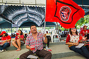 01 MAY 2013 - BANGKOK, THAILAND: A man waves the Red Shirt flag during a Red Shirt protest at the Thai Constitutional Court. Several hundred Thai Red Shirts, members of the United Front for Democracy against Dictatorship (UDD), have been camped out at Thailand's Constitutional Court, which oversees matters related to the Thai constitution and constitutional amendment. The Red Shirts are protesting the court's decision to consider a petition regarding the constitutionality of the constitutional amendments that have been proposed by the government. The group is arguing that by considering the petition, the Court is impeding the powers of the legislative branch.   PHOTO BY JACK KURTZ