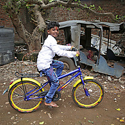 MUMBAI, INDIA - JUNE, 27, 2017: Nine-year-old Sunny Pawar, pictured on his new bicycle outside his home in a slum in Mumbai, India.<br />