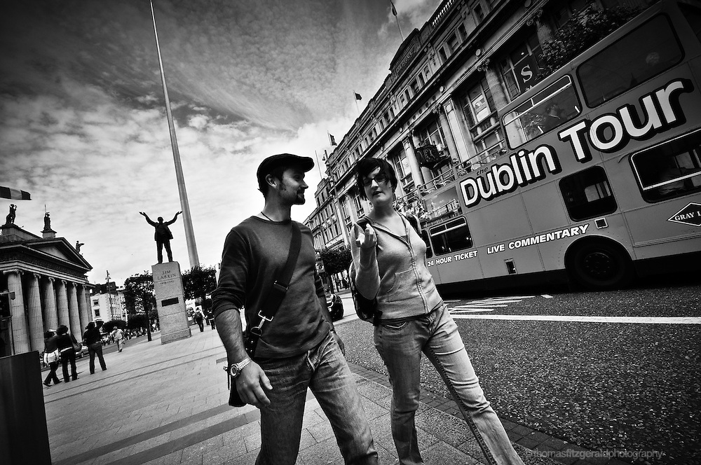A Pair Of Tourists walk down O'Connell Street in Dublin, with a tour bus in the background and the Spire and the GPO behind them. <br />