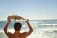 Man holding surfboard above head by ocean back view head and shoulders