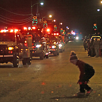 Fire trucks make their way down Nettleton Main Street for the town's Christmas parade.