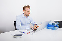 Mid-adult businessman working on laptop at desk in office