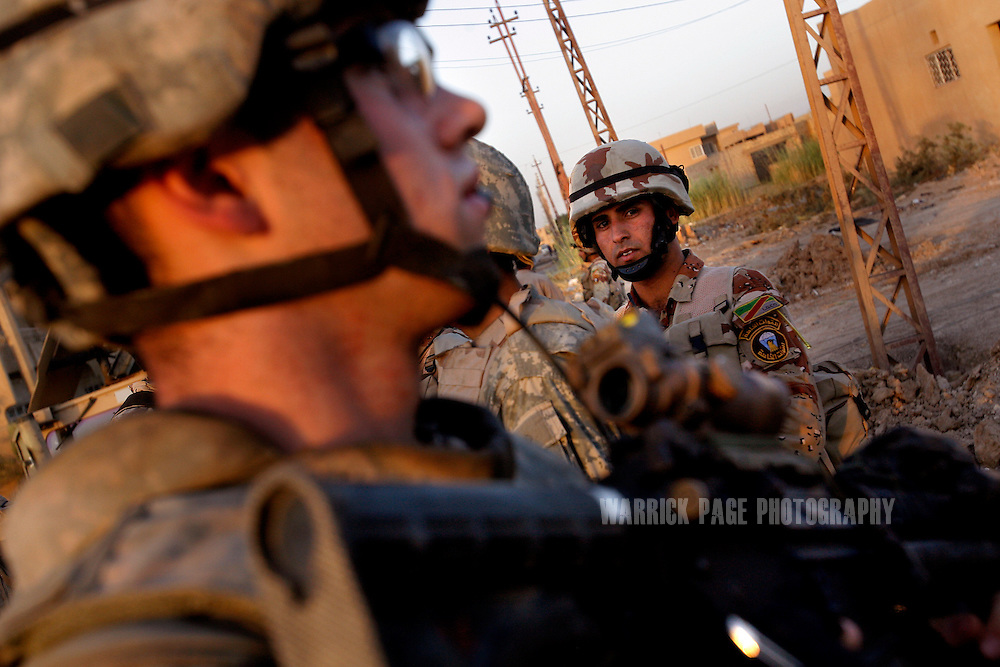 BAGHDAD, IRAQ - JUNE 25: A US soldier with Alpha Company, 4th Battalion, 6th Armoured, 4th Brigade, 3rd Infantry Division, conducts a patrol with Iraqi forces in the suburb of Sadiyah, June 25, 2008, Baghdad, Iraq. Neighbourhoods like Sadiyah became a battleground for Shiite militias and Sunni extremists after the bombing of the Golden Mosque in Samarra in 2006. Tens of thousands of people were either forced out of their homes or fled the violence to neigbouring countries or other parts of Iraq. Now predominantly Shiite, Sadiyah is being used as a test case by the Iraqi government to encourage the millions who have fled - many of which have the skills and money to rebuild the country. Since early 2008, Iraq's security situation has improved with oil production is increasing, record government surplus and easing sectarian tensions. (Photo by Warrick Page)