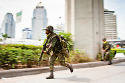May 19 - BANGKOK, THAILAND: Thai soldiers run under cover along Ratchadamri Road in Lumpini Park during the Thai government crack down against Red Shirt and anti government protesters. The Royal Thai Army attacked anti-government protesters May 19 with troops and armored personnel carriers. PHOTO BY JACK KURTZ