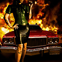 Conceptual image of young adult female dressed in latex with tattoos holding baseball bat standing beside red car with flames