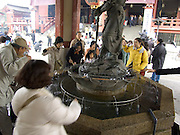 people drinking water at the Asakusa Kannon Temple Tokyo