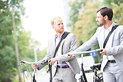 Businessmen looking at each other while holding bicycles outdoors