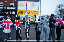"© Licensed to London News Pictures . 11/01/2013 . Belfast , UK . Loyalist protesters stand in the middle of the road opposite the office of the Alliance Party on the Newtownards Road in East Belfast today (11th January 2013) ahead of "" Operation Standstill "" . The protest is one of many that have been held since Belfast City Council voted to stop flying the Union flag above Belfast City Hall . Photo credit : Joel Goodman/LNP."