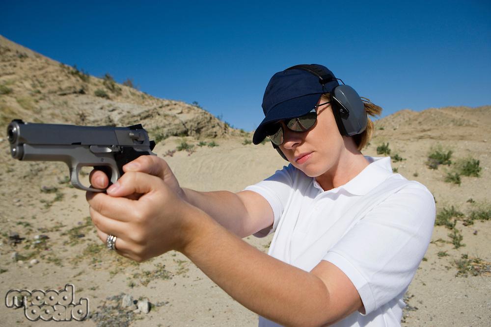Woman aiming hand gun at firing range in desert