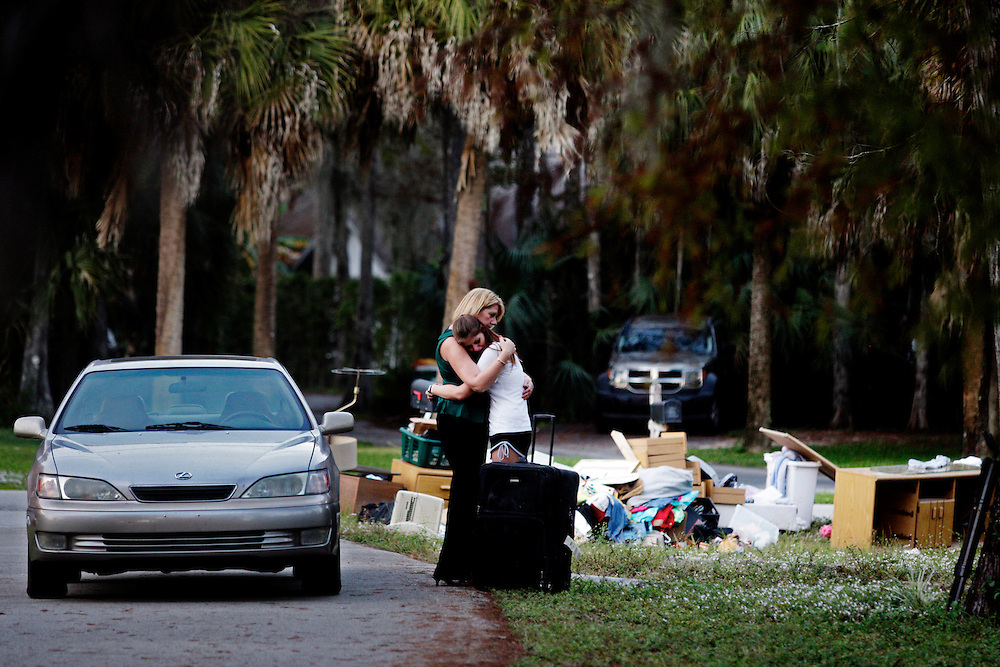 Denise Brunal-Hicks, left, hugs her daughter, Samantha, 18, as they stand next to a curb piled with their belongings. Brunal-Hicks was being evicted from her foreclosed home after spending thirteen years at the residence. Her only option was to take her two children and temporarily live in a spare room at her brother's place across town. Greg Kahn/Staff