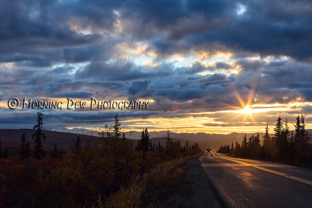 The sun begins to set on a cloudy autumn day as a shuttle bus drives along the Denali Park Road.