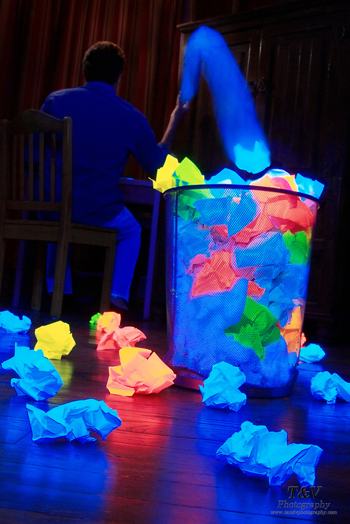 A man tosses a glowing piece of paper into a wastebasket overflowing with crumpled paper.