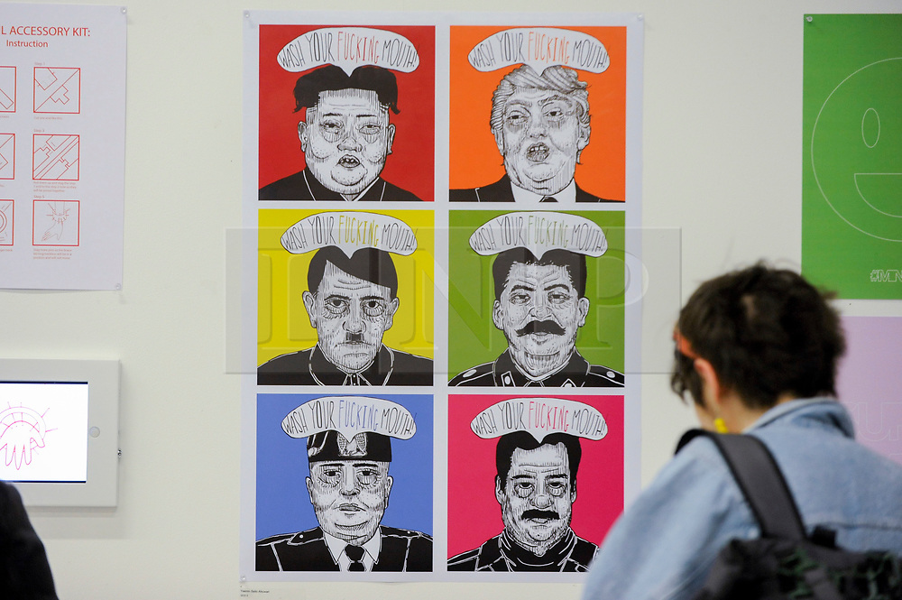 "© Licensed to London News Pictures. 11/05/2017. London, UK. A visitor views a work, featuring current and past political figures, by Yasmin Saito Alkuwari at an exhibition called ""Up and Coming"", in Granary Square King's Cross.  The exhibition includes works by Central Saint Martins foundation students.   Photo credit : Stephen Chung/LNP"