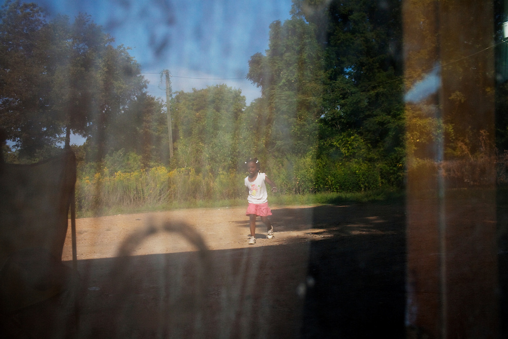 Dialia Wooten plays in front of the home she shares with her mother and two siblings just across the train tracks from the Baptist Town neighborhood of Greenwood, Mississippi on Sept. 25, 2010. Dialia's father is in prison and her family was evicted from their home in the Baptist Town neighborhood earlier in the year.