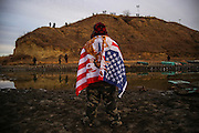 Andrew Waupekenay of the Menominee Indian Tribe of Wisconsin stands as he faces authorities on the other side of the Cantapeta Creek which runs into the Missouri River after barbed wire was placed along the shore near the Oceti Sakowin Camp on Army Corps of Engineers land bordering the Standing Rock Indian Reservation in Cannon Ball, North Dakota in November 2016.<br /> <br /> A $3.8 billion project by Energy Transfer Partners to construct a 1,172-mile pipeline transporting crude Bakken oil from North Dakota across South Dakota, Iowa and into Illinois has sparked conflict and controversy at a key construction site on US Army Corps land bordering the Standing Rock Indian Reservation.