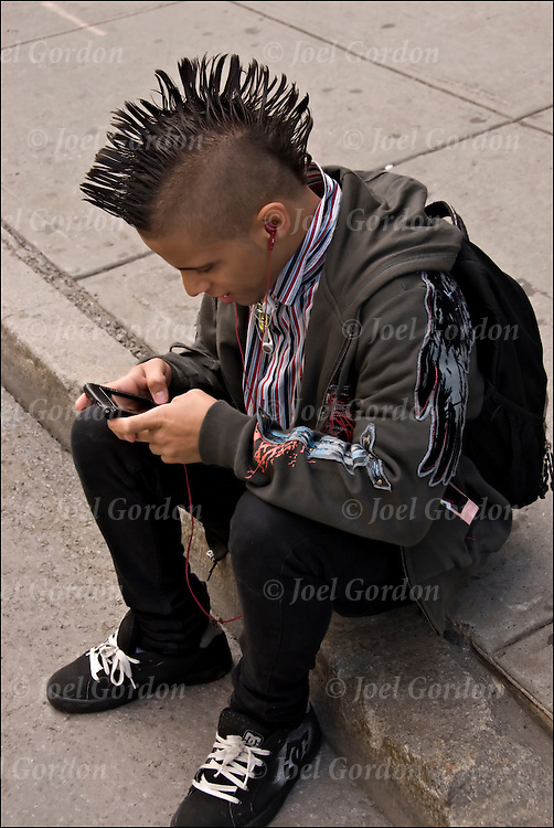 15 year old teenage rocker with mohawk haircut listening to music on ipod