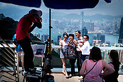 China, Hong Kong - Mainland Chinese tour group (more than half of all visitors come from the mainland), at Stubbs Road Lookout with its view over Hong Kong Island and its skyscrapers on May 01, 2018. A view from the Sky Terrace on top of Victoria Peak.  the 'concrete jungle' that constitutes the entanglement of buildings in Hong-Kong, China. The former British territory is the city with the most skyscrapers in the world.