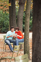 Couple reading guide book sitting on chairs in park