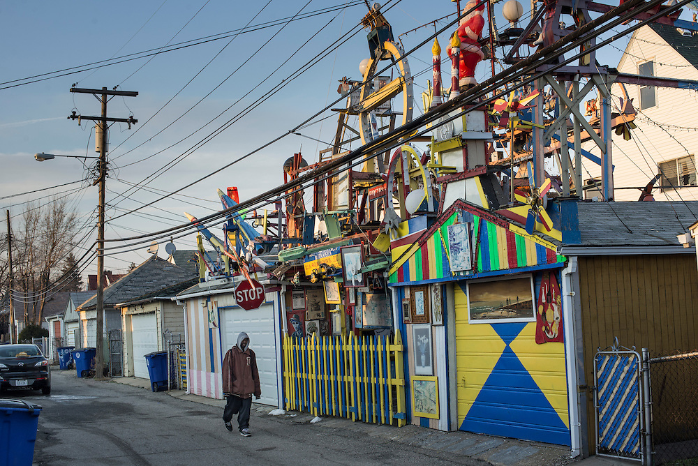 "A man walking past Ukrainian immigrant Dmytro Szylak's  artwork called ""Hamtramck Disneyland"" in Hamtramck, Detroit. . Szylak started building it after he retired from his job at General Motors."