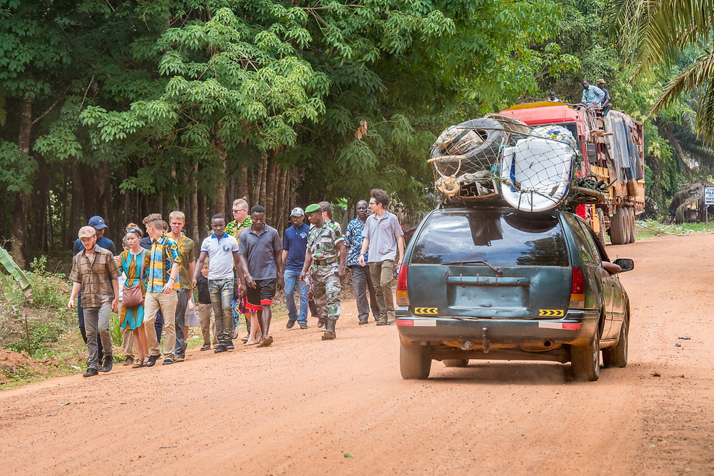 Group of students and tour guides walk together on dirt road as a car  packed with various household items drives past, Republic of Guinea
