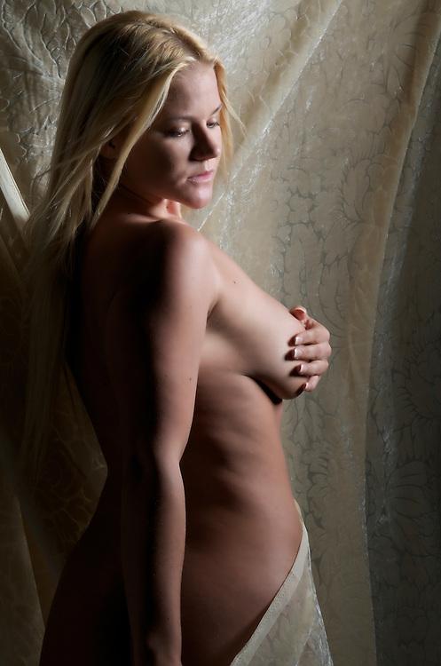 Sensual blonde posing nude with drape