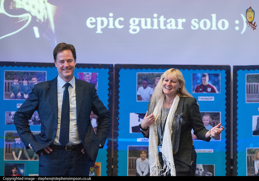 © Licensed to London News Pictures. 13/10/2014. London, UK. Nick Clegg stands with Executive Head Teacher Karen Bastick-Styles as she plays air guitar with the pupils.  The Deputy Prime Minister, Nick Clegg, visits Greenside Primary School in Shepherd's Bush on Monday 13th October 2014 to launch a new campaign called Primary Futures – a new strand of the Inspiring the Future campaign. Photo credit : Stephen Simpson/LNP