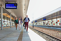 Portrait of business people running to catch the train in station