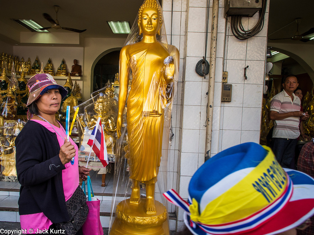 05 JANUARY 2014 - BANGKOK, THAILAND:  Anti-government walk past a shop selling statues of the Buddha in Bangkok. Suthep Thaugsuband, leader of the anti-government protests in Bangkok, led the protestors on a march through the Chinatown district of Bangkok. Tens of thousands of people waving Thai flags and blowing whistles gridlocked what was already one of the most congested parts of the city. The march was intended to be a warm up to their plan by protestors to completely shut down Bangkok starting Jan. 13.     PHOTO BY JACK KURTZ