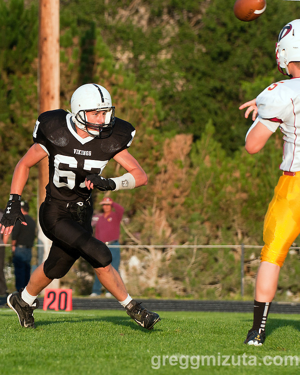 Ontario quarterback Trampis Waite gets the pass off before Vale's Levi Maag can get to him on September 16, 2011 in Vale, Oregon.