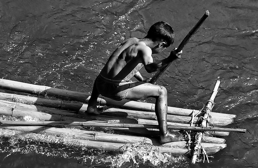 Boys play with their bamboo rafts on the Mekong river at Tha Duea, Laos.