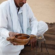 Bishnoi man making opium drink for welcome ceremony