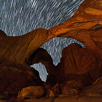 Double Arch painted with light in Arches National Park near Moab Utah with star trails under the dark skies.