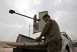 © Licensed to London News Pictures. 28/09/2014. Rabia, Iraq. A fighter belonging to the Syrian-Kurdish YPG works next to a 23mm heavy machine gun at a YPG position in the Iraqi border town of Rabia.<br /> <br /> Facing each other across the Iraq-Syria border, the towns of Al-Yarubiyah, Syria, and Rabia, Iraq, were taken by Islamic State insurgents in August 2014. Since then The town of Al-Yarubiyah and parts of Rabia have been re-taken by fighters from the Syrian Kurdish YPG. At present the situation in the towns is static, but with large exchanges of sniper and heavy machine gun fire as well as mortars and rocket propelled grenades, recently occasional close quarter fighting has taken place as either side tests the defences of the other. Photo credit: Matt Cetti-Roberts/LNP