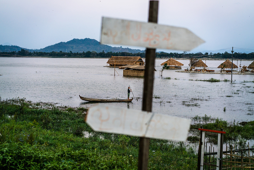 MYITKYINA, MYANMAR - MARCH 11th, 2016:  A man fishes from a small boat near a floating restaurant on the Irrawaddy River.