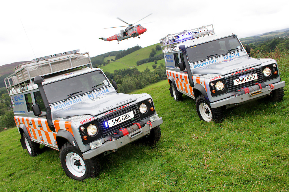 Tweed Valley Mountain Rescue unit taking delivery of two new of road 'ambulance' Land Rovers, with the RAF search and resuce helicopter hovering overhead