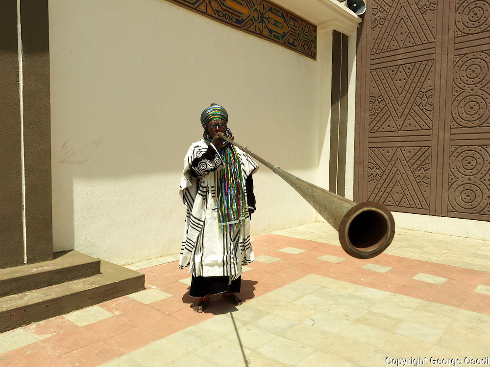 Court musician play kakaki horn outside the Emir of Kano's palace