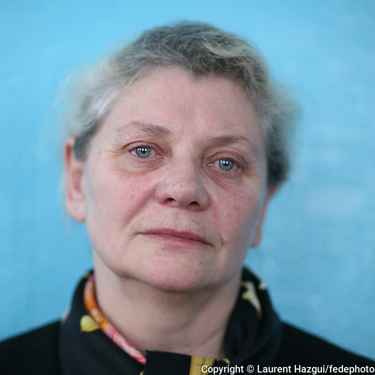 """Dans le Nord de l'Ukraine, Lidia Olexiivna Bernikova est inconsolable de la mort de son fils, autant que de l'évacuation forcée de sa ville de Poliské. Elle est revenue y habiter et franchi chaque jour le point de passage de la zone interdite, pour diriger l'école de la ville voisine de Lugoviki. Cette dernière a perdu les trois quarts de ses élèves comparé à avant la catastrophe. L'association """"Les enfants de Tchernobyl"""" Alsace aide cette école avec du don de matériel scolaire."""
