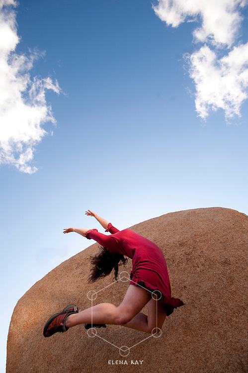 Female dancer in a red dress leaping up into an abstract sky-stone landscape.<br />