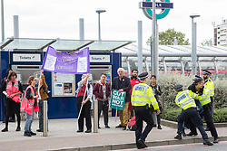 London, UK. 3 September, 2019. Metropolitan Police officers prevent an activist from blocking a road in front of a truck arriving at ExCel London on the second day of a week-long carnival of resistance against DSEI, the world's largest arms fair. The second day's events were organised around a theme of No Faith In War and were attended by representatives of many faith groups including a significant number of Quakers.