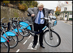The London Mayor Boris Johnson lifts up a Barclays Bike as he expands the Barclays Cycle Hire to Wandsworth, South West London, United Kingdom. Friday, 13th December 2013. Picture by Andrew Parsons / i-Images