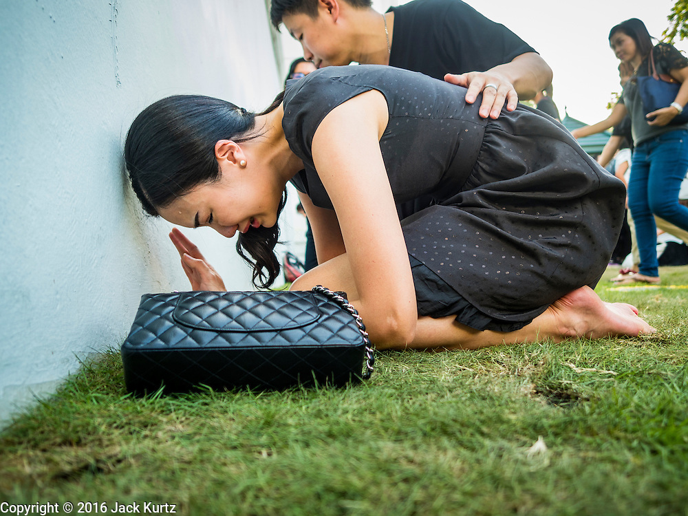15 OCTOBER 2016 - BANGKOK, THAILAND: A woman in mourning weeps and prays in front of the Grand Palace for Bhumibol Adulyadej, the King of Thailand. King Bhumibol Adulyadej died Oct. 13, 2016. He was 88. His death comes after a period of failing health. With the king's death, the world's longest-reigning monarch is Queen Elizabeth II, who ascended to the British throne in 1952. Bhumibol Adulyadej, was born in Cambridge, MA, on 5 December 1927. He was the ninth monarch of Thailand from the Chakri Dynasty and is known as Rama IX. He became King on June 9, 1946 and served as King of Thailand for 70 years, 126 days. He was, at the time of his death, the world's longest-serving head of state and the longest-reigning monarch in Thai history.      PHOTO BY JACK KURTZ