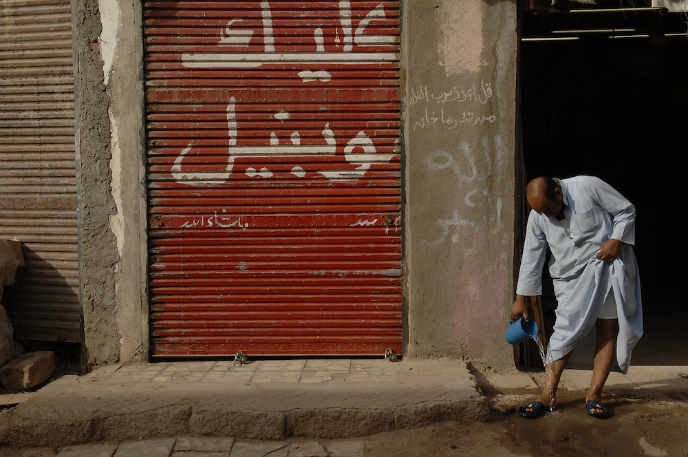 Man washes his feet in street in Aswan, Egypt.