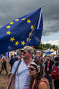 A dissapointed couple are cheered by a comedian in the Greenpeace area whilst showing their support for the EU with its flag, under stormy skies - The 2016 Glastonbury Festival, Worthy Farm, Glastonbury.