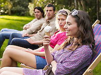 Group of young people sitting in row on deckchairs in garden side view