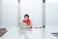 Woman smiling by laptop in modern cubicle