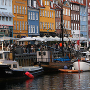 Nyhavn or New Harbor, is a 17th-century waterfront, canal and entertainment district in Copenhagen. Stretching from Kongens Nytorv to the harbor front just south of the Royal Playhouse, it is lined by brightly painted 17th and early 18th century townhouses, bars, cafes and restaurants. <br /> <br /> Photography by Jose More