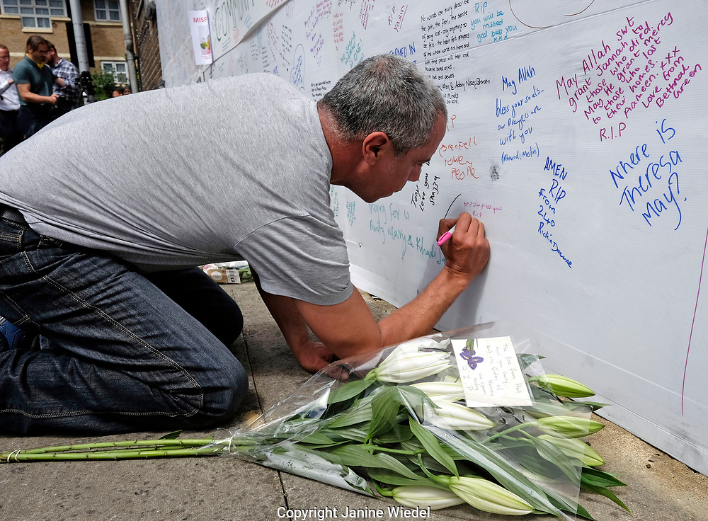 Families and friends writing on the wall of condolence in the aftermath of the fire that destroyed the 24-story Grenfell Tower in North Kensington, London on 14th June 2017.  The death toll officially at 75 but will no doubt rise to three figures.