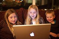 Children sitting in sofa with an Apple laptop computer. Two girls with their brother. Glow from the computer screen in their faces. Krakkarnir með fartölvuna í stofusófanum heima í Sandavaði.