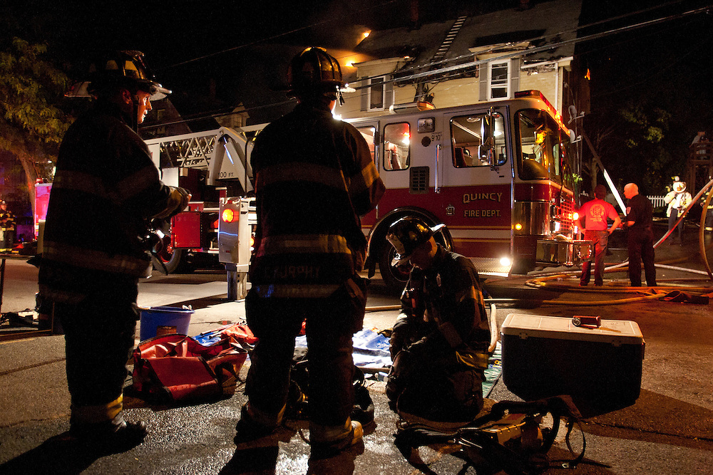 Quincy, MA 10/09/2011.Quincy Fire Department firefighters prepare to don their air tanks at the scene of a 2 alarm house fire at 44 Penn St. on Sunday night..Alex Jones / www.alexjonesphoto.com